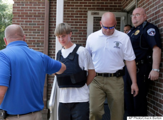 Charleston, S.C., shooting suspect Dylann Storm Roof, center, is escorted from the Sheby Police Department in Shelby, N.C., Thursday, June 18, 2015. Roof is a suspect in the shooting of several people Wednesday night at the historic The Emanuel African Methodist Episcopal Church in Charleston, S.C. (AP Photo/Chuck Burton)