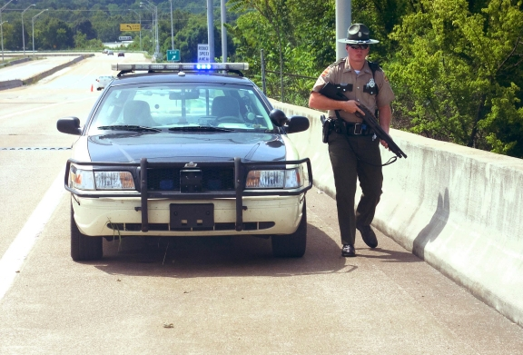Tennessee Highway Patrol Trooper Paul Clendenen guards the top of the C.B. Robinson Bridge at Amnicola Highway after a morning shooting near the Naval Reserve Center, in Chattanooga, Tenn. on Thursday, July 16, 2015.  Chattanooga Mayor Andy Berke said there's