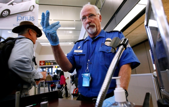 FILE - In this Jan. 4 2010 file photo, TSA officer Robert Howard signals an airline passenger forward at a security check-point at Seattle-Tacoma International Airport, in SeaTac, Wash. The Transportation Security Administration will allow you to keep your laptop in your bag during the screening process if the bag will produce a clear and unobstructed image of the laptop when undergoing X-ray screening.(AP Photo/Elaine Thompson, file)