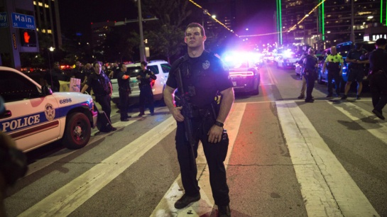 A Police officer stands guard at a baracade following the sniper shooting in Dallas on July 7, 2016. A fourth police officer was killed and two suspected snipers were in custody after a protest late Thursday against police brutality in Dallas, authorities said. One suspect had turned himself in and another who was in a shootout with SWAT officers was also in custody, the Dallas Police Department tweeted. / AFP / Laura Buckman (Photo credit should read LAURA BUCKMAN/AFP/Getty Images)